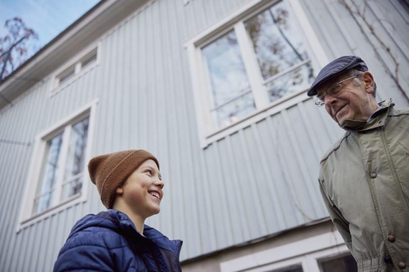 Poika ja vanhempi mies katsovat toisiaan ja hymyilevät.