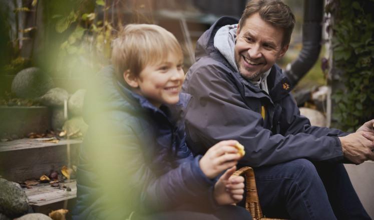 Mies ja poika istuvat ulkona ja hymyilevät.
