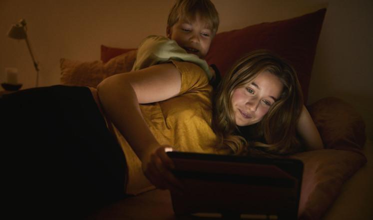 Teini-ikäinen tyttö ja nuorempi poika makaavat sängyllä ja katsovat tietokonetta.