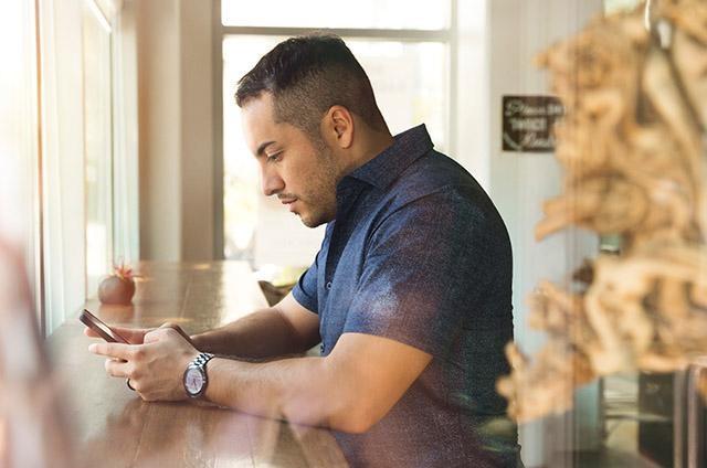 Mies selaamassa puhelintaan