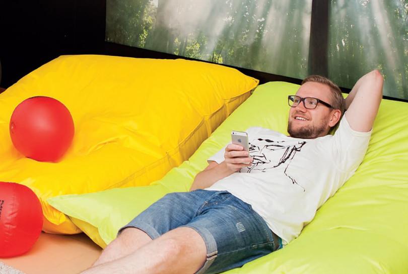 Jukka Hietamäki makoilee säkkityynyn päällä ja hymyilee.