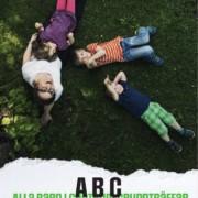 Tre barn och en vuxen ligger på en gräsmatta