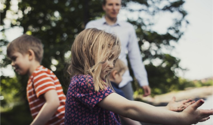 Lekande barn i förgrunden, en man i bakgrunden
