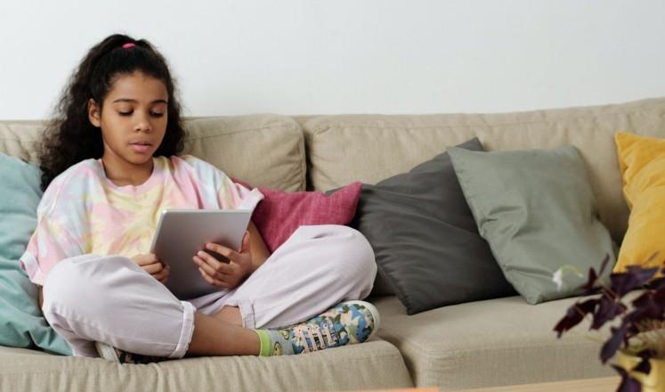Lapsi istuu sohvalla padi kädessä