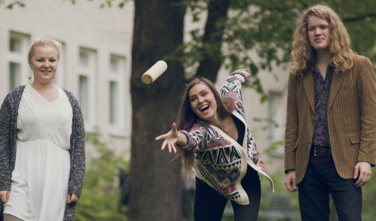 Iloiset ja aktiiviset nuoret pelaavat mölkkyä puistossa