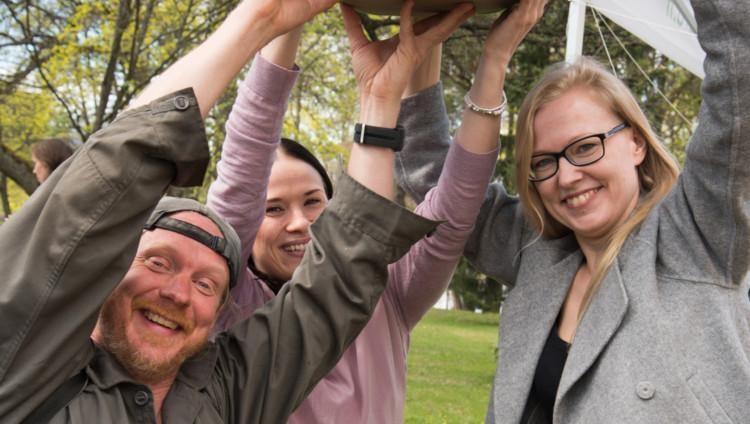 Iloiset vapaaehtoiset nostavat yhdessä jotain päänsä yläpuolelle