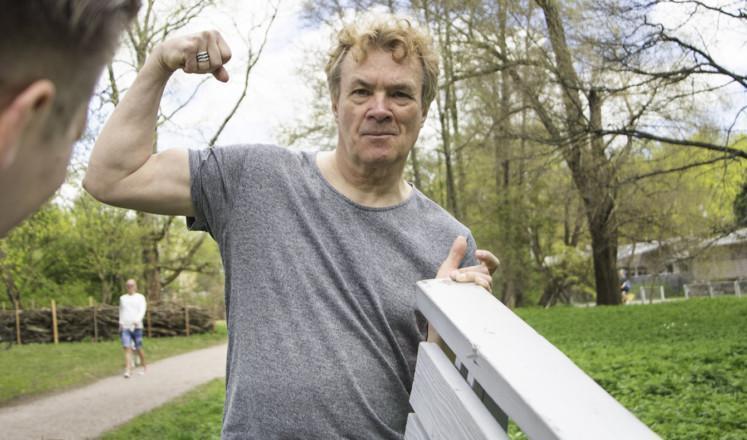 Mies nostaa puistonpenkkiä hyväntyuulisena toisen kanssa yhdellä kädellä ja näyttää hauista toisella