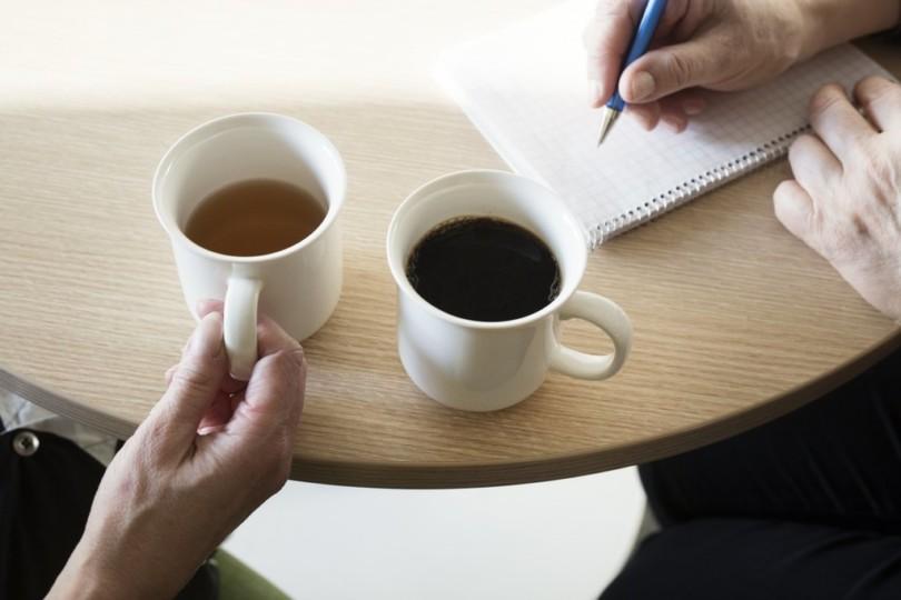 Kaksi kahvimukia ja kädet pöydällä