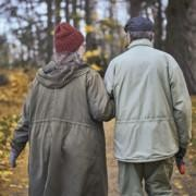 Nainen ja mies kävelevät syksyisessä metsässä.