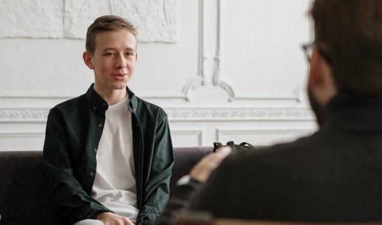 Nuori mies keskustelee auttajan kanssa