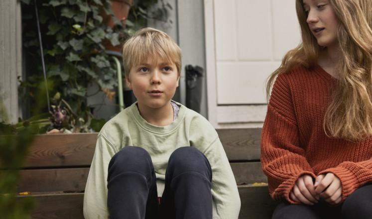 Poika ja tyttö istuvat portailla