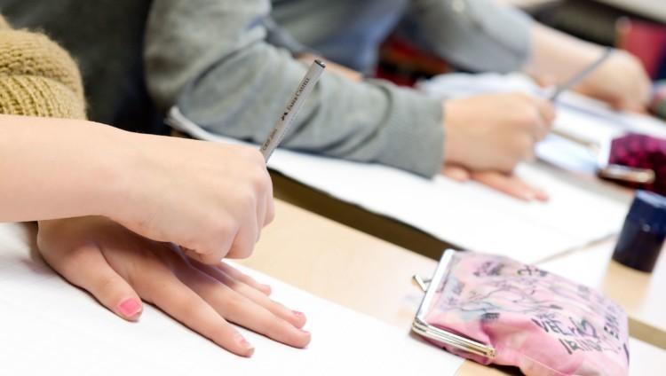 Koululaiset piirtävät paperille.