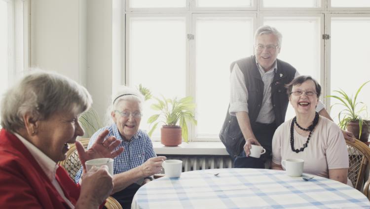Ryhmä iloisia kä-ihmisiä kahvipöydän äärellä