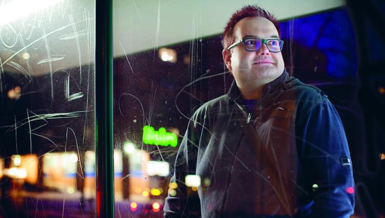 Jani Verho seisoo ratikkapysäkillä yöllä.