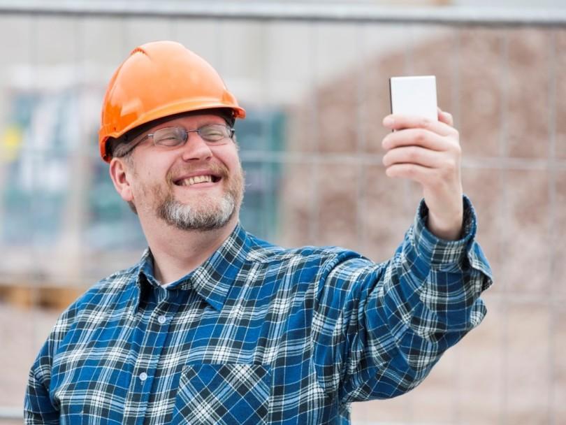 Hymyilevä mies työmaakypärä päässä