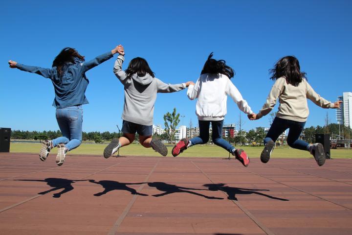 Tytöt hyppäävät auringossa
