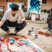 Mies maalaa lattialla