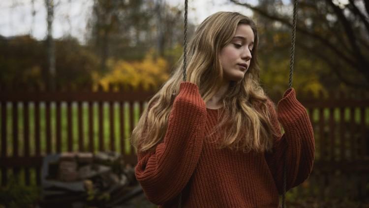Apeailmeinen teinityttö istuu keinussa syksyllä