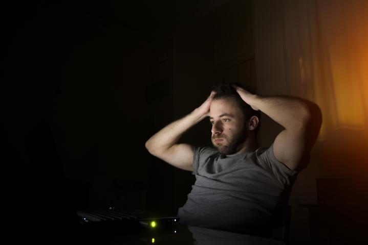 Mies katsoo tietokoneen näyttöä uupuneena