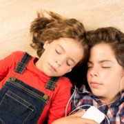 Kaksi lasta kuuntelee musiikkia kuulokkeista silmät kiinni