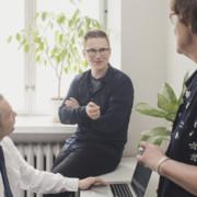 Kolme henkilöä juttelee iloisesti toimistohuoneessa