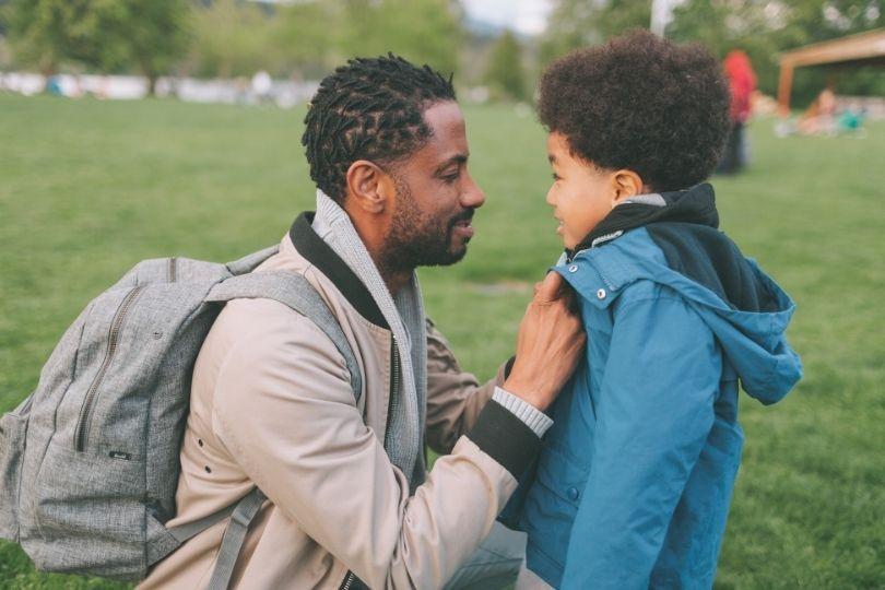 Isä korjaa pojan takkia. Molemmat hymyilevät.
