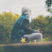 Nuori istuu ulkona huppu päässä